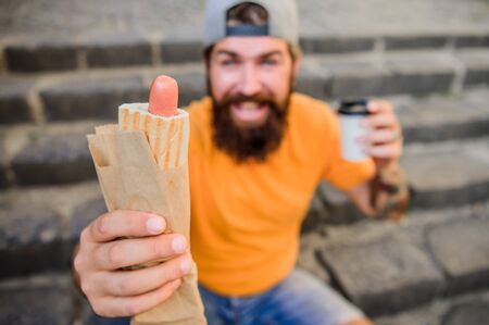Carefree hipster eat junk food while sit on stairs. Hungry man snack. Guy eating hot dog. Man bearded bite tasty sausage and drink paper cup. Street food so good. Urban lifestyle nutrition. Junk food