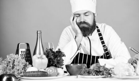 Bored chef lean on table at kitchen. Culinary inspiration. Hard day at restaurant. Tired and exhausted chef. Man bearded chef cooking food. Chef fed up of boring meals. Looking for inspiration