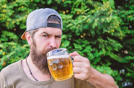 Beer and ale concept. Man relaxing enjoying beer hot summer day. Quench thirst. Alcohol drink and bar. Hipster brutal bearded man hold mug cold fresh beer. Craft beer is young, urban and fashionable Banco de Imagens