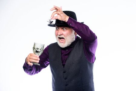 Disgusting Halloween drink. Elegant bartender wear hat and vest prepare drink. Halloween concept. Add spider cocktail recipe. Horror themed Halloween party. Weird old grandfather with gray beard