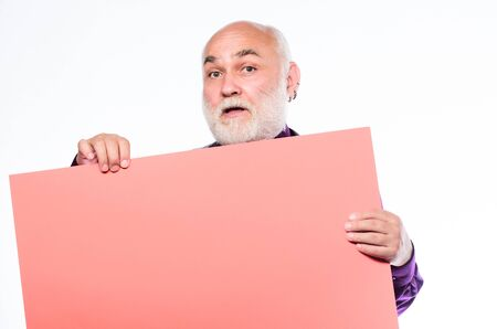 Senior holding blank sign board and looking at camera. Elderly people. Man bold head and gray beard hold poster for advertisement copy space. Senior means experienced. Senior man recommend something Фото со стока