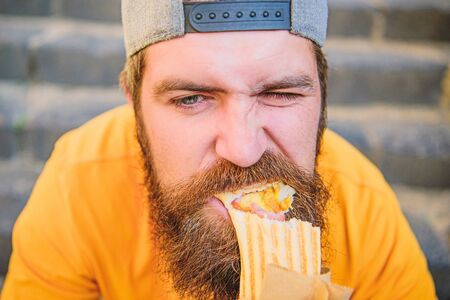 Junk food. Snack for good mood. Unleashed appetite. Street food concept. Man bearded eat tasty sausage. Urban lifestyle nutrition. Carefree hipster eat junk food while sit stairs. Guy eating hot dog Фото со стока