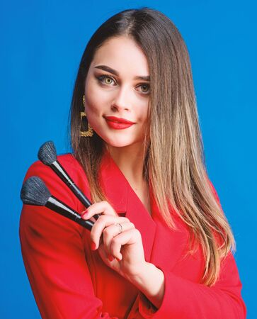 Pure beauty. Sexy woman with professional makeup brush tool. jewelry earrings. Girl in red jacket. beauty and fashion. hair beauty and hairdresser salon. Fashion portrait of woman