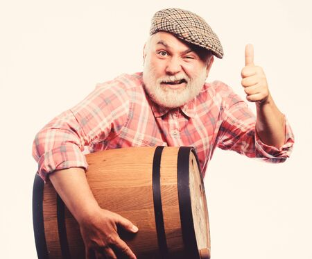 Winery concept. Homemade wine. Producing wine family tradition. Man bearded senior carry wooden barrel for wine white background. Fermentation product. Natural wine made out of organic grapes 写真素材