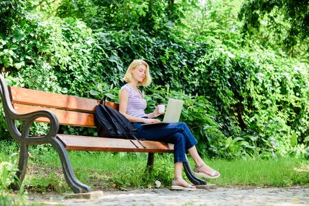 Surfing internet. Girl adorable student with laptop and coffee cup sit bench in park. Study outdoors. Woman student work with notebook. Learn study explore. Modern student life. Regular student