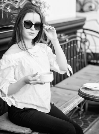 Breakfast time in cafe. Girl enjoy morning coffee. Woman in sunglasses drink coffee outdoors. Girl relax in cafe cappuccino cup. Caffeine dose. Coffee for energetic successful day. Waiting for date Stock fotó - 129811832