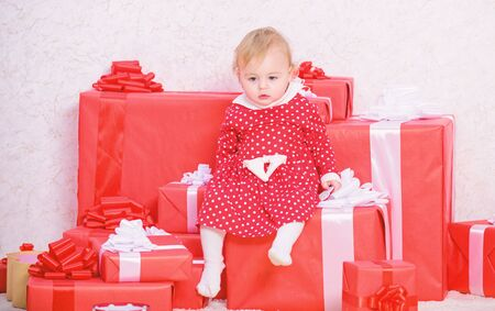 Little baby girl play near pile of gift boxes. Gifts for child first christmas. Celebrate first christmas. Baby first christmas once in lifetime event. Sharing joy of baby first christmas with family