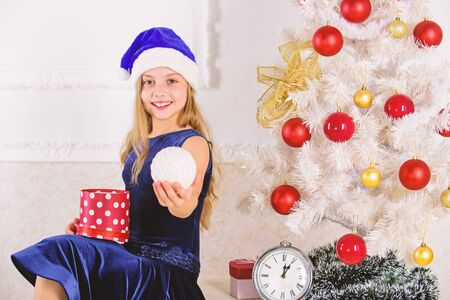 Happy new year concept. Kid girl sit near christmas tree hold gift box. Little girl santa hat excited about christmas gift or present. Child celebrate christmas at home. Time to open christmas gifts