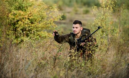 Bearded serious hunter spend leisure hunting. Man wear camouflage clothes nature background. Hunting permit. Hunter hold rifle. Hunting is brutal masculine hobby. Hunting and trapping seasons
