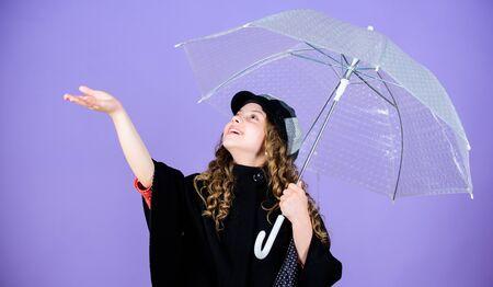 Enjoy rainy weather with proper garments. Waterproof accessories make rainy day fun. Enjoy rain concept. Fall season. Kids fashion trend. Love rainy days. Kid girl happy hold transparent umbrella Foto de archivo - 129823385