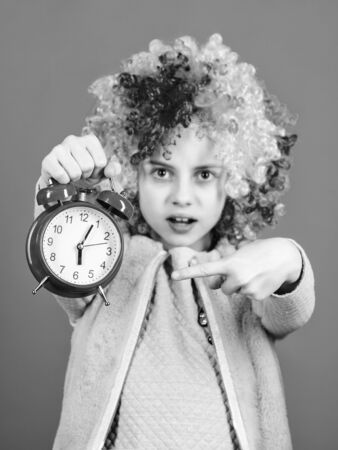Girl worry about time. Time to have fun. Discipline and time concept. Circus performance timing. Kid colorful curly wig clown style hold alarm clock. I am not joking about discipline. False alarm