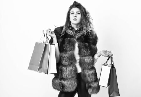 Girl makeup furry coat shopping white background. Shopping or birthday gifts. Woman shopping luxury boutique. Lady hold shopping bags. Discount and sale. Fashionista buy clothes on black friday Stock Photo