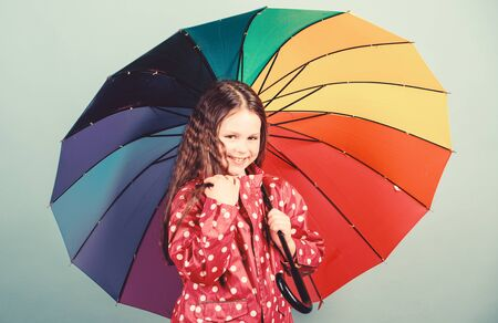 cheerful hipster child in positive mood. rain protection. Rainbow. happy small girl with colorful umbrella. Small girl in raincoat. autumn fashion. Feeling the nature. So beautiful