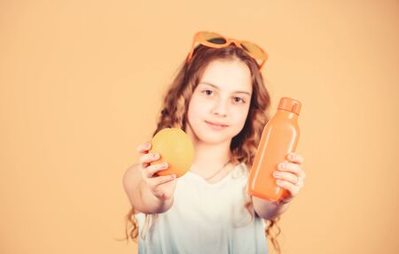 Health in her hands. Natural vitamin source. happy girl drink fresh orange juice. summer vacation. little girl in glasses. Vitamin nutrition. refreshing vitamin juice. Health care. vitamin diet