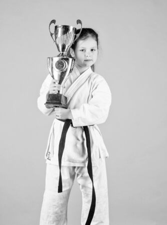 knockout. energy activity for kids. small girl with champion cup. martial arts. practice Kung Fu. happy childhood. sport success in single combat. winner little girl in gi sportswear. Simply the best
