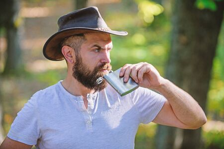 Guy brutal bearded cowboy drink alcohol metal flask. Hipster with beard drink alcohol nature background defocused. Hiking camping. Wanderer concept. Alcohol drink. Nomadic man carry alcohol with him