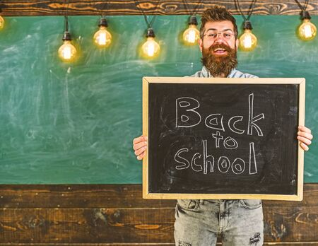 High school concept. Teacher in eyeglasses holds blackboard with title back to school. Man with beard and mustache on cheerful smiling face welcomes students, chalkboard on backgroun