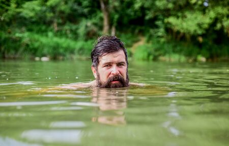wild man. time to relax. bearded man swimming in lake. summer vacation. mature swimmer. brutal hipster with wet beard. refreshing in river water. water beast. furry monster
