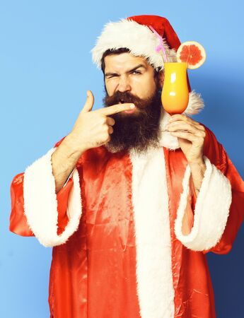 handsome bearded santa claus man with long beard on serious face holding glass of nonalcoholic cocktail in christmas or xmas sweater and new year hat shows on it on blue studio backgroun Zdjęcie Seryjne