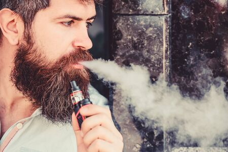 Man with beard breathe out smoke. Smoking electronic cigarette. Stress relief concept. Smoking device. Man long beard relaxed with smoking habit. Clouds of flavored smoke. Bearded man smoking vape
