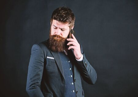 Searching for right decision. Bearded man with smartphone. brutal caucasian hipster. businessman in suit. Male formal fashion. business communication. Mature hipster with beard speak on phone