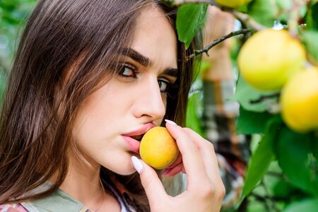Enjoying eating apricot. natural cosmetics. perfect skin. fashion makeup beauty. juicy fruit. woman near apricot. Orchard. organic food and vitamin. fitness and dieting. healthy lifestyle