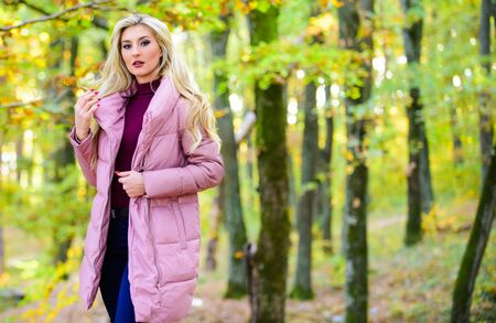 Cold blonde concept. How to repair bleached hair fast and safely. Autumn hair care is important so as to avoid dry frizzy hair. Girl fashionable blonde walk in autumn park. Autumn hair care concept