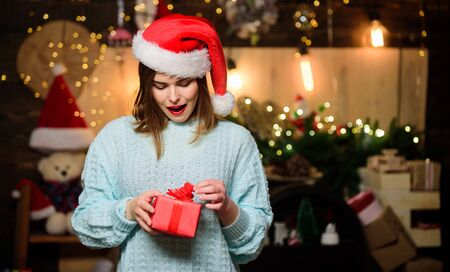 Believe in miracle. Woman santa claus hat on christmas eve. Lady adorable cute face celebrate christmas at home. Girl stylish makeup red lips making christmas wish. Cozy christmas atmosphere