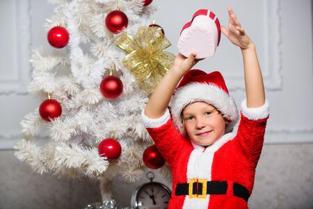 Christmas santa claus costume for child. Christmas party with santa costume. Christmas tree ideas for kids. Boy kid dressed as santa with red hat hold gift box near christmas tree
