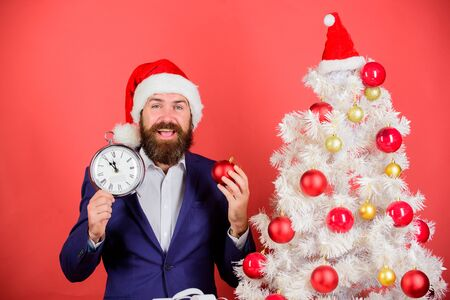 Keep track of time. Time to celebrate. Businessman join christmas celebration. Man bearded wear suit and santa hat hold clock. Last minute deals. Counting time till christmas. How much time left