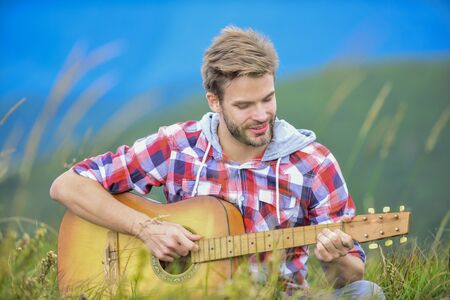 Hiking song. Man musician with guitar on top mountain. Inspired musician. Hipster musician. Inspiring environment. Summer music festival outdoors. Silence of mountains and sound of guitar strings 写真素材