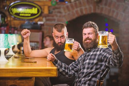 Alcohol drinks. Friends relaxing in pub with beer. Refreshing beer concept. Men drinking beer together. Hipster brutal man drinking beer with friend at bar counter. Men drunk relaxing having fun
