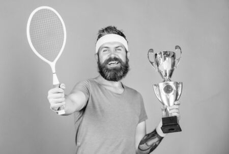 No player can step on court against me and feel confident. Tennis player win championship. Athlete hipster hold tennis racket and golden goblet. Win tennis game. Man bearded hipster wear sport outfit