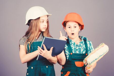 Little kids in helmet with tablet and roller. Labor day. 1 may. small girls repairing together in workshop. Foreman inspector. Repair. engineering idea. my idea is perfect. let me introduce my idea