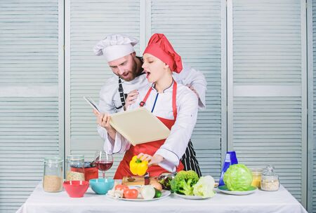 Amateur cook read book recipes. Improve cooking skill. Book recipes. Helpful culinary book. Woman chef and man cooking food together. Culinary family concept. Couple in love cooking healthy recipe