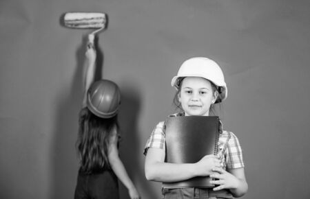 Little kids in helmet with tablet and roller. Labor day. 1 may. engineering idea. Future career. Painting wall. Foreman inspector. Repair. small girls repairing together in workshop. working day