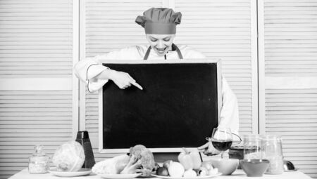 Your product is here. Master cook presenting something at cooking class. Pretty woman pointing finger at blackboard. Chief cook teaching in cooking school. Master class in culinary school, copy space Banque d'images