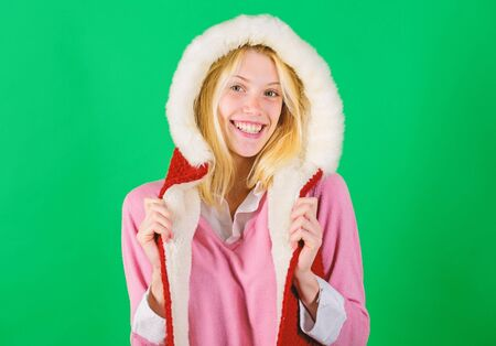 Woman emotional face posing in warm furry hood. Winter time for cozy warm accessories. Lets stay warm in fur clothing. Girl cheerful blonde warming up wear fur hood on green background
