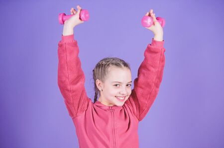 Happy child sportsman with dumbbell. workout of small girl hold dumbbell. weight lifting for muscules. Childhood activity. Fitness diet for energy health. Sport success. Exercising with dumbbells 写真素材