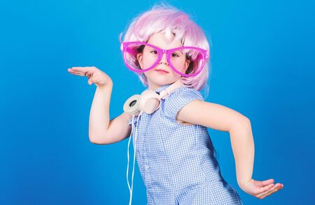 Cute kid with headphones blue background. Small girl headphones pink wig dancing. Child using technology for fun. Modern headphones. Energy motion dance. Inspired by music. Little kid listening music