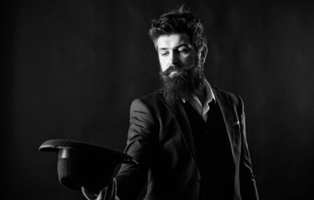 Man well groomed bearded gentleman on dark background. Male fashion and menswear. Formal suit classic style outfit. Elegant and stylish hipster. Retro fashion hat. Man with hat. Vintage fashion