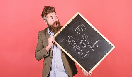 Teaching stressful occupation. Stay positive. Teacher with tousled hair stressful about school year beginning. Teacher bearded man holds blackboard with inscription back to school red background