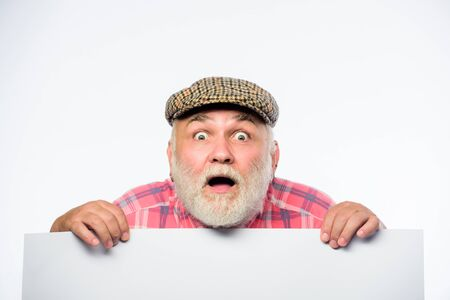 Elderly person. Announcement concept. Event announcement. Senior bearded emotional man peek out of banner place announcement. Pensioner grandfather in vintage hat poster information copy space Banque d'images - 129432794