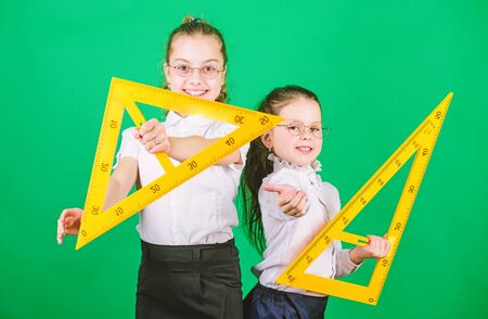 Geometry favorite subject. Education and school concept. School students learning geometry. Kids school uniform green background. STEM school disciplines. Classmates cute girls with big rulers