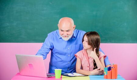 Modern knowledge. Schoolgirl and tutor with laptop. Modern education. Happy student. Modern teaching method. Student girl with teacher man at blackboard. Senior teacher and girl at school lesson