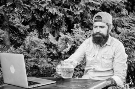 Bearded hipster freelancer enjoy end of working day with beer mug. He deserve this pint. Brutal man leisure with beer and online game. Finally friday. Hipster relax sit terrace outdoors with beer