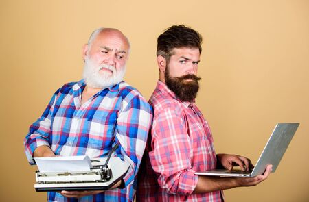two bearded men. Vintage typewriter. father and son. technology development and improvement. retro typewriter vs laptop. technology generation battle. Modern life. youth vs old age. business approach