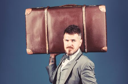 heavy bag. mature traveller. bearded man in formal suit. stylish esthete with vintage bag. businessman in bow tie. business trip with retro suitcase. Elegance and style. Trendy and handsome Stockfoto