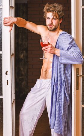 Bachelor sexy body chest and belly. Sexy attractive macho tousled hair coming out through bedroom door. Guy shimmering sweaty skin wear bathrobe. Man with sexy torso drink wine. Sexy lover concept