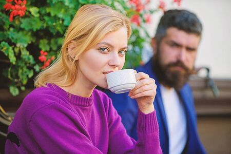 problem in relationship. woman and man with beard relax in cafe. Couple in love on romantic date. First meet of girl and mature man. Morning coffee. Brutal bearded hipster and girl drink coffee Фото со стока